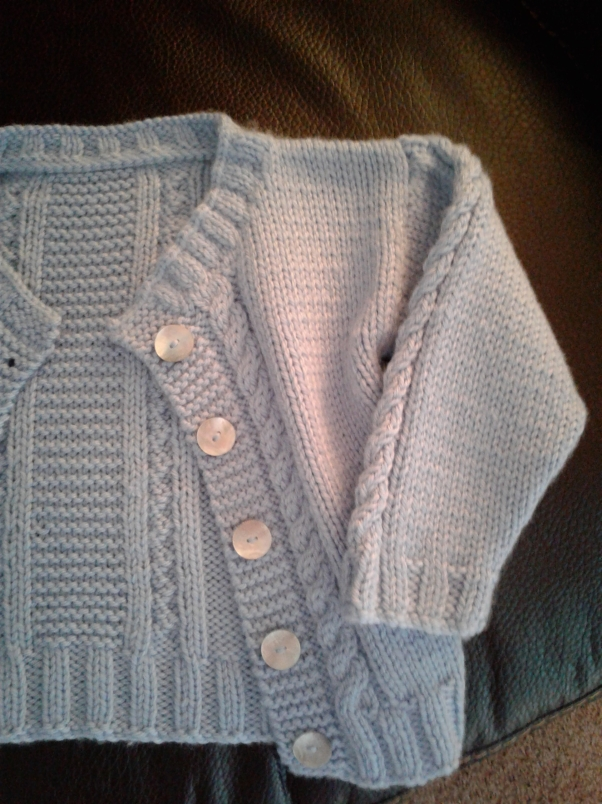 Baby blue cardigan with mother-of-pearl buttons.