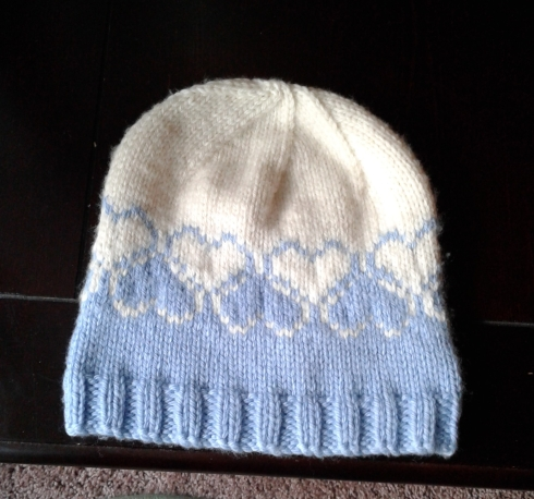 Child's knitted hat with heart pattern, in white and blue