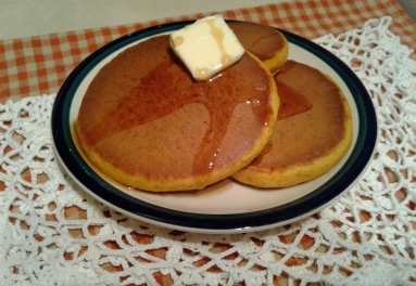 Soft, fuffy pumpkin spice pancakes on a plate with maple syrup and a pat of butter