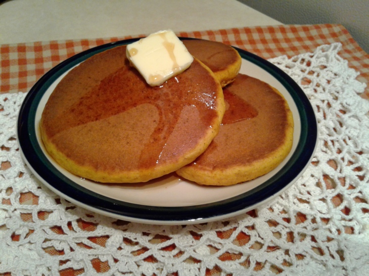 Plate of pumpkin spice pancakes with butter and maple syrup
