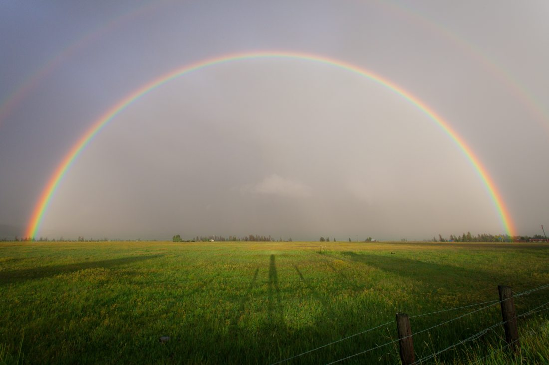 rainbow shining over a green field