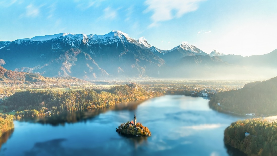 Island in the middle of Bled Lake in Slovenia, with the mountains in the distance