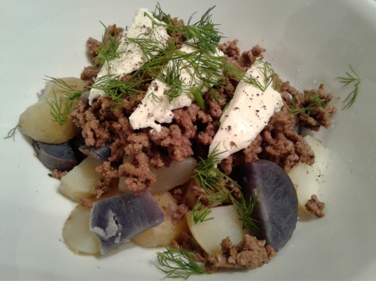 Purple and white potatoes topped with ground beef and sour cream