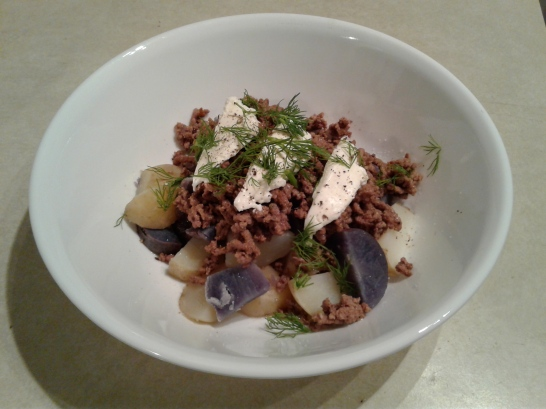 Boiled purple and white potatoes with ground beef and sour cream