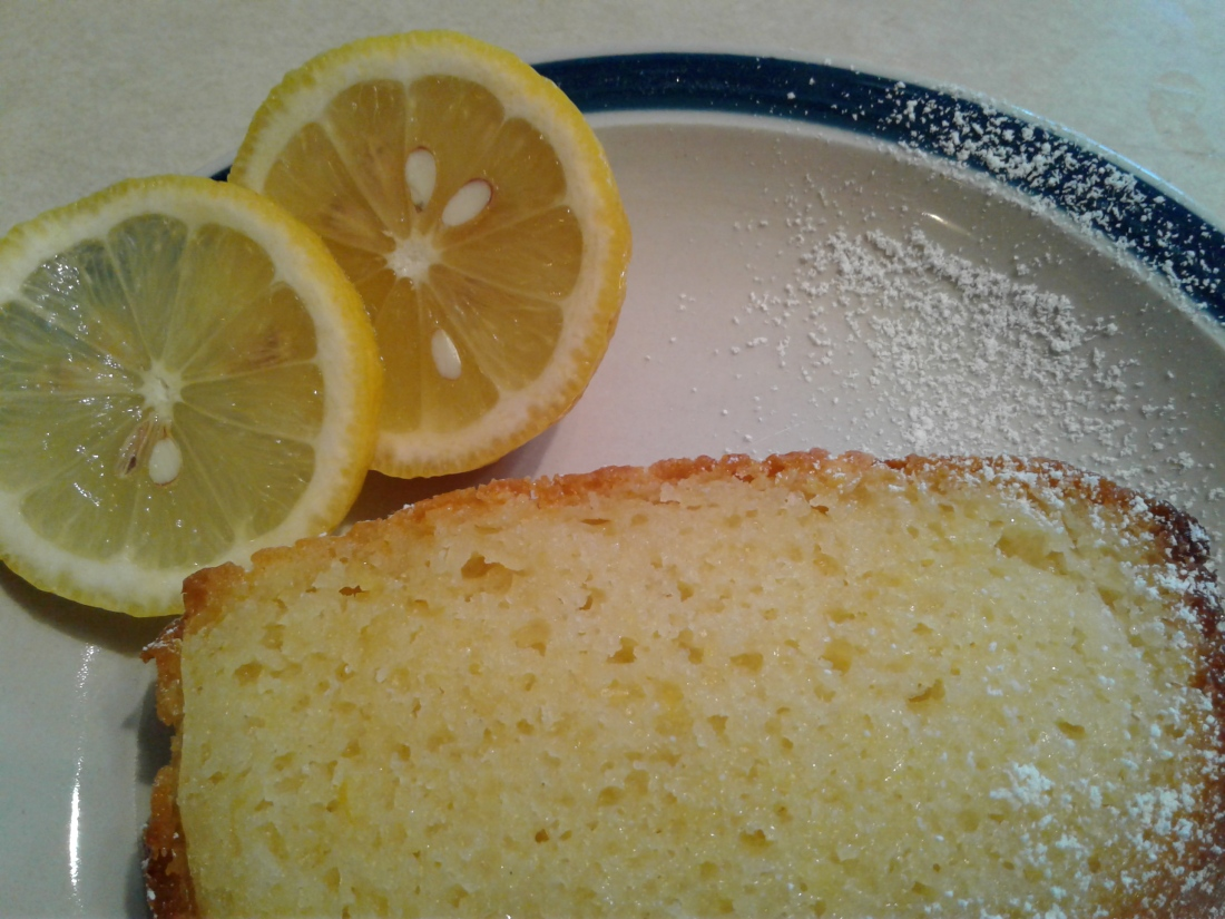 Beautiful lemon cake on plate with lemon rounds and powered sugar