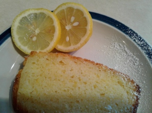 Lemon yogurt cake slice with lemons on the side