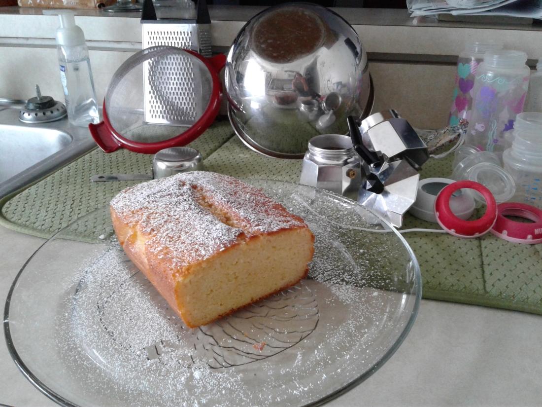Lemon yogurt cake in front of moka espresso pot and dishes