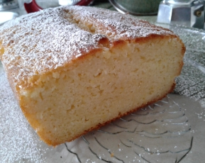 Lemon yogurt cake on a glass plate with powdered sugar