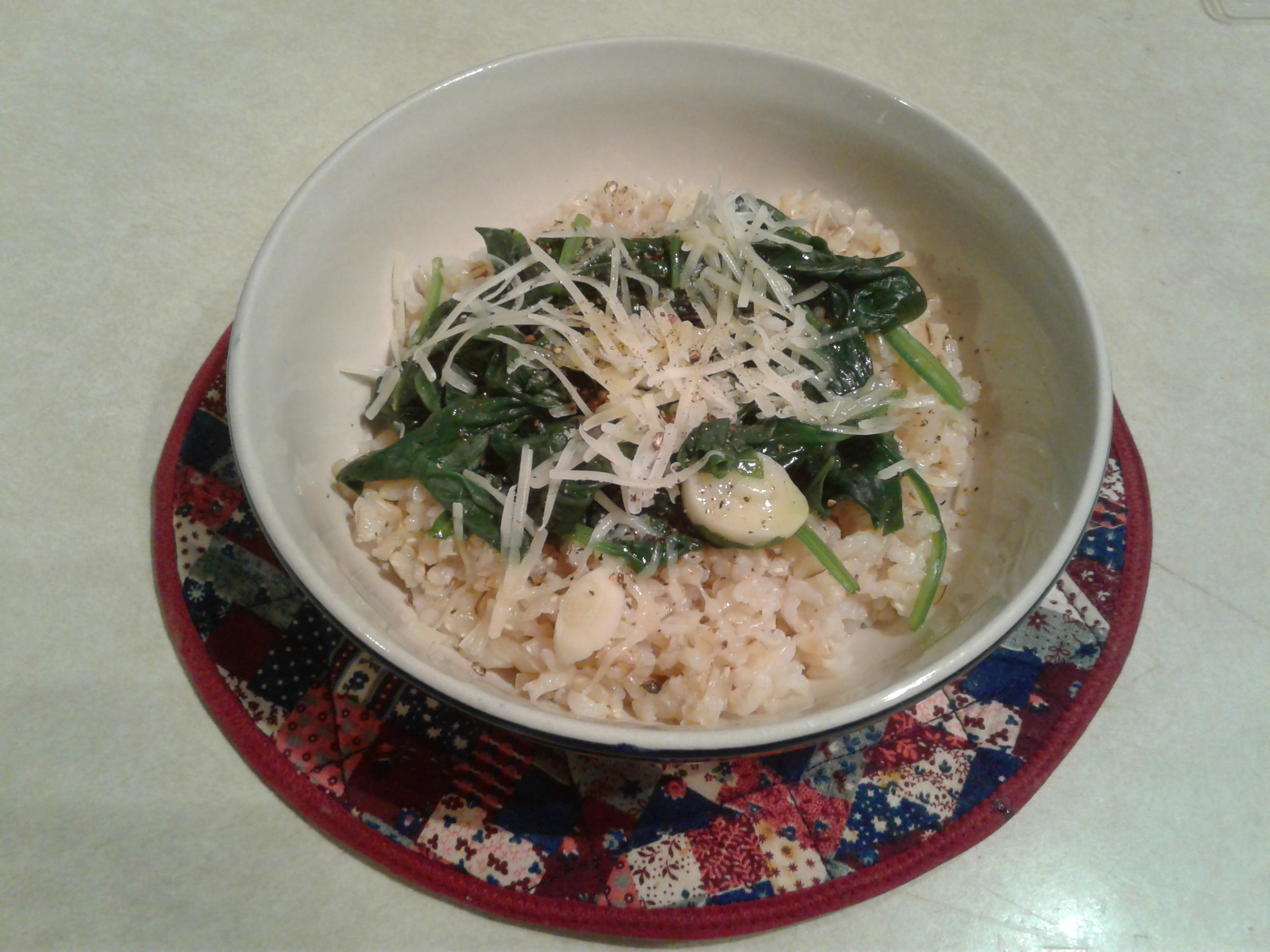 Bowl of brown rice and spinach, topped with parmesan