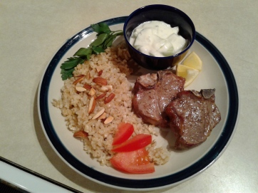 Plate of lamb chops, rice and yogurt cucumber sauce
