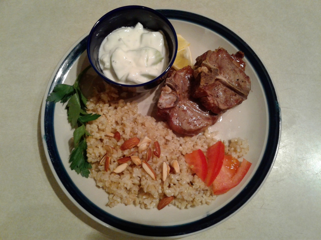 Lamb chops on a plate with cucumber yogurt sauce and brown rice
