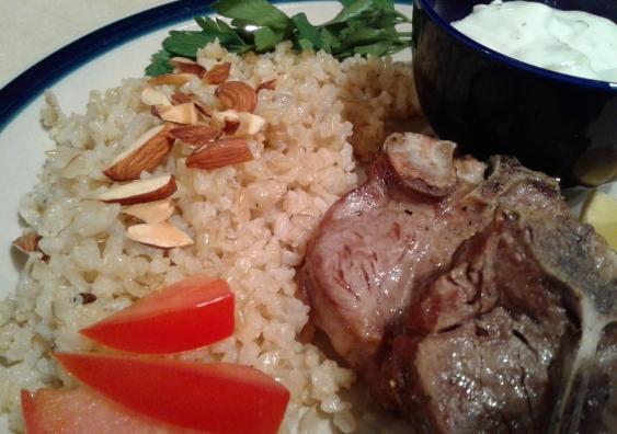 Plate of lamb chops, rice and yogurt cucumber sauce