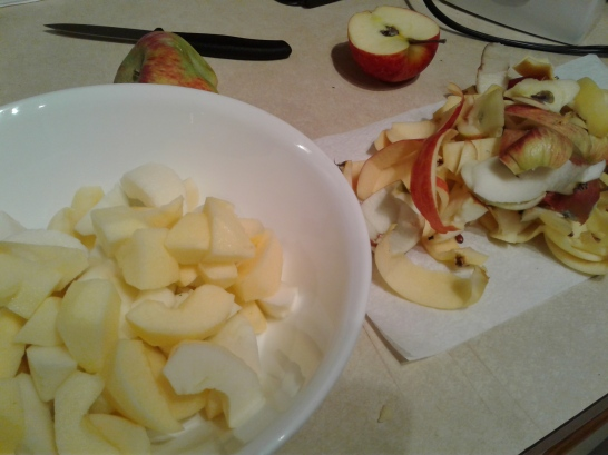 Bowl of apples slices with the apple peels nearby