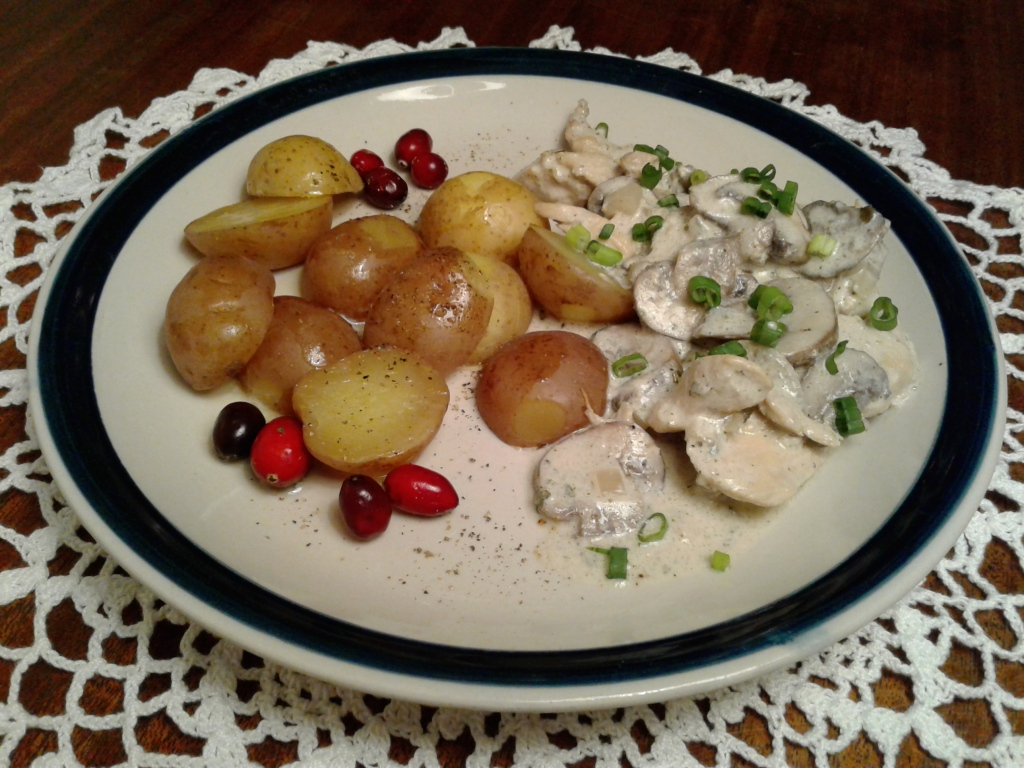 Plate of creamy chicken and mushrooms with sage and a side of potatoes