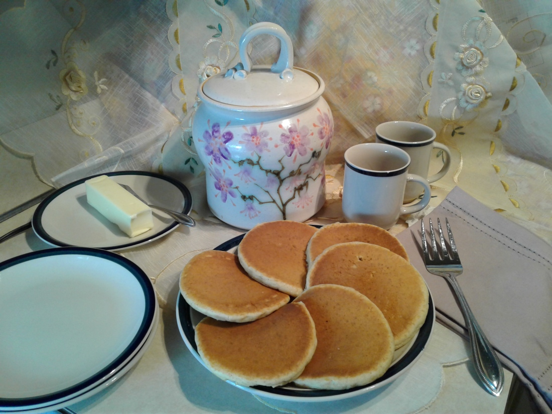 Plate of pancakes with butter and table settings
