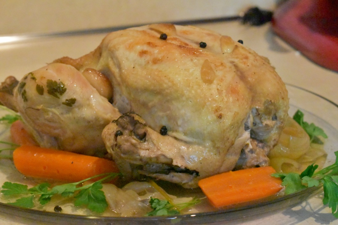 Roast chicken on a platter with carrots, onions, and parsley